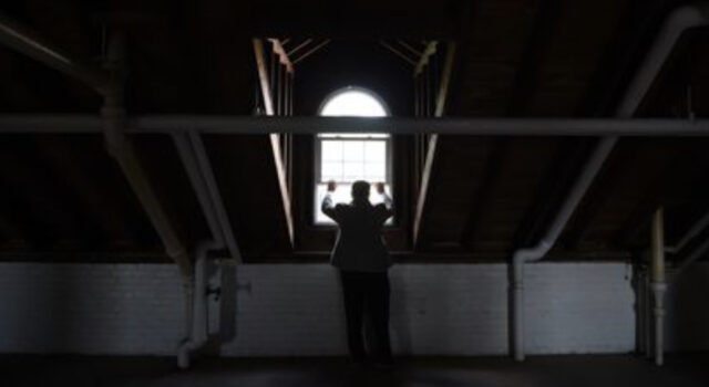 Founder Marty Kenny looking out window at historic building
