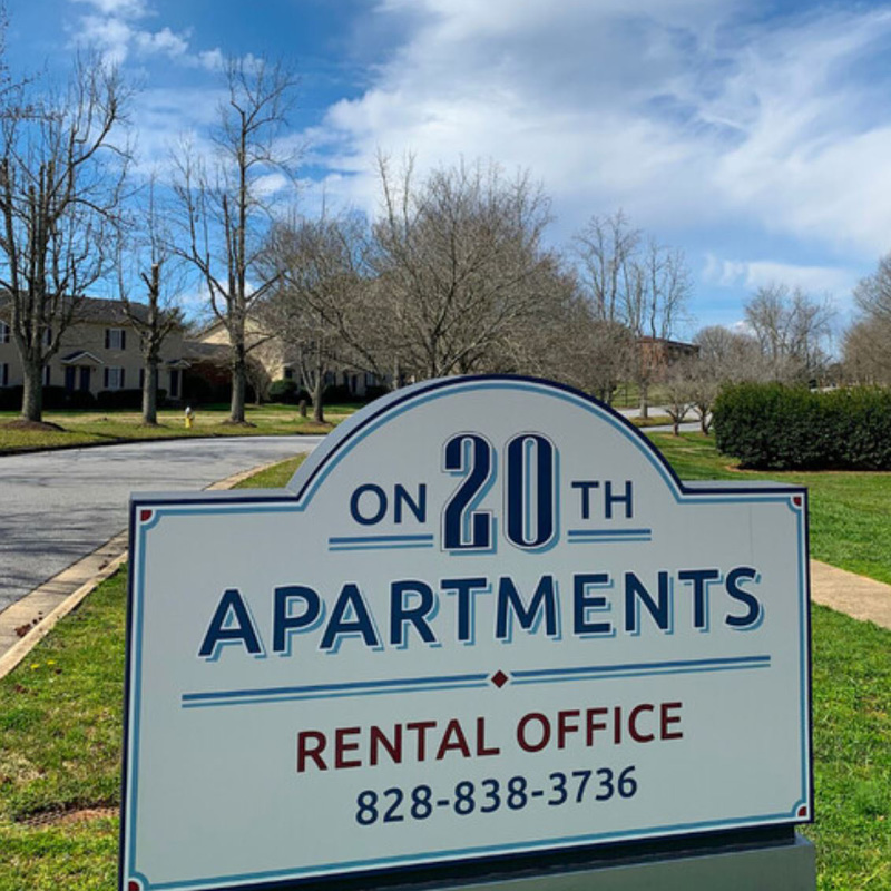 Apartment sign with modern logo and blue and red with trees and grass in background