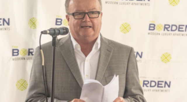 Man with suit speaking at an event with backdrop