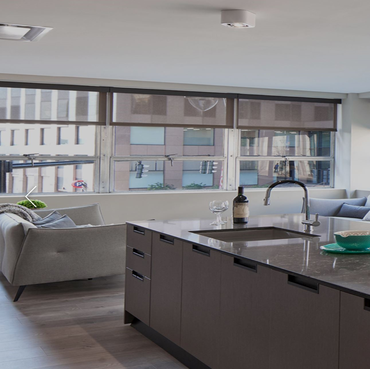 Kitchen with modern cabinets and quartz countertops with white couch and cool windows in background